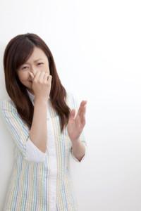 臭いに鼻をつまむ女性